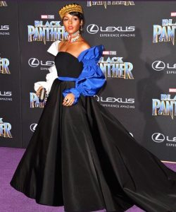 "The royal purple carpet at Monday night's world premiere of ""Black Panther"" was awash in gem tones and African-inspired prints as those privileged to catch the film early adhered to Disney's ""royal attire"" dress code. The lavish event staged on Hollywood Boulevard outside the Dolby Theatre, where the film bowed, took its cues from the movie's hero — King T'Challa (Chadwick Boseman), ruler of the fictional African country of Wakanda, who also masquerades as the tech-forward superhero Black Panther. Just over two weeks ahead of the film's wide release on Feb. 16, the cast and other members of the Marvel Cinematic Universe took to the carpet to muse about the importance of representation, and why this film couldn't have come at a better time. Check out the standout fashion from the ""Black Panther"" premiere » ""Being in a Trump era right now, how timely it is to actually see black representation onscreen,"" said Denzel Whitaker, who plays Young Zuri in the film. ""To see pride onscreen. To see different facets of black culture onscreen. To see us in different representations of intelligence, of power, of presence."" ""We're now finally having the opportunity to see heroes that look, sound and feel like us,"" agreed Cheo Hodari Coker, executive producer of Netflix's ""Marvel's Luke Cage."" ""Growing up, I always loved ['Star Wars' hero] Luke Skywalker, I always loved Han Solo, but there was always a disconnect because I knew that I could never really be them. ""And from a standpoint of pride, it's [palpable],"" he continued. ""There's something about it that I think is special. To see this kind of story be told with a real budget and our superstars I think is going to be an amazing experience."" Lupita Nyong'o,who plays Nakia in ""Black Panther,"" at the films Los Angeles world premiere. (Chris Pizzello / Invision/AP) 1 / 25 Among those superstar cast members, Oscar nominated icon Angela Bassett, who plays T'Challa's mother in the film, and newly minted Oscar nominee Daniel Kaluuya (who plays W'Kabi) also weighed in on the significance of seeing oneself reflected onscreen. ""It's always important throughout the end of time,"" Kaluuya said simply. ""It's always important for young kids to see themselves."" ""I brought my kids here tonight because I want them to see it,"" said Bassett. ""Tonight, to see all of this brilliance not only with T'Challa but with his brilliant sister Shuri [played by breakout actress Letitia Wright] — all of that is inspiration for these kids."" Laura Harrier, who played Peter Parker's love interest Liz in last year's ""Spider-Man: Homecoming,"" is also happy to both see and be a part of the newfound inclusion in superhero blockbusters. ""That's what's been so cool about Marvel right now,"" she said. ""There weren't love interests in Spider-Man movies that looked like me until there was me. There weren't black superheroes [onscreen] until right now. It's amazing that things are changing and we're starting to see films reflect modern times."" On whether she could imagine a Spider-Man/Black Panther crossover in the future, Harrier's fingers are crossed. ""I hope so and I hope I'm in it. I'd like to see them teaming up, beating the bad guys. Hopefully Liz makes a cameo and she's in Wakanda too,"" she said with a laugh. ""Maybe they'll adopt me, I don't know."" Mike Colter, who plays Luke Cage in the Netflix series, would also like to see a crossover in the future. Or at least access to T'Challa's wardrobe. ""Give me something that when you shoot it, it leaves no holes so I don't have to change my clothes,"" he said. ""I know I'm bulletproof, but I want a suit for practical purposes. That's all I'm asking for."" Just as long as Luke and T'Challa don't butt heads. ""If I catch him out of his suit, he's done,"" said Colter. Angela Bassett and Daniel Kaluuya at the Los Angeles World Premiere of Marvel Studios' ""Black Panther"" at Dolby Theatre. Angela Bassett and Daniel Kaluuya at the Los Angeles World Premiere of Marvel Studios' ""Black Panther"" at Dolby Theatre. (Jesse Grant / Getty Images for Disney) Florence Kasumba, whose ""Black Panther"" character Ayo first appeared in ""Captain America: Civil War"" admitted that she has never seen a superhero that has looked like her until recently. ""The first time I saw a superhero like me?"" she said. ""I think when I watched 'Civil War!'"" Bassett first saw herself reflected onscreen through Halle Berry's Storm in the ""X-Men"" films. ""But ['Star Trek' communications officer] Lieutenant Uhura [played by Nichelle Nichols] was a superhero to us,"" she said. ""Conquering space! She was a superhero."" For Coker, his first brush with a supe was closer to home. ""My grandfather was a Tuskegee Airman that flew in with the 100th Fighter Squadron,"" he said. ""So I grew up seeing black men doing things that no one else thought they could and it inspired me to do the same thing."" Though representation among the superhero canon is certainly long overdue, it would be remiss to attribute T'Challa's popularity solely to his skin color. Clark Gregg, who played S.H.I.E.L.D. agent Phil Coulson in the ""Iron Man"" films and now on ABC's ""Agents of S.H.I.E.L.D.,"" agrees that the Black Panther is so much more. ""I've gotten to watch all these different chapters play out,"" he said. ""And yet when I was a kid in the '70s reading these comics...when we saw Black Panther, it was different. At that time, a lot of the characters that African Americans were playing on TV were pimps. And to see this guy that was a king who went to Oxford, who ruled this country and was magnificent...my friends and I really freaked out about this. ""I'm geeking out tonight,"" Gregg continued. ""This is a very different part of the world and everything about it looks very special."""