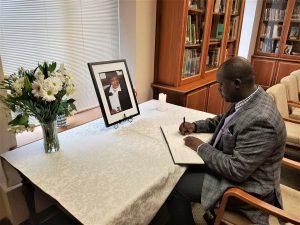 Adesanmi filling a condolence register in 2018