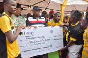 Pic 3- L-R: Team captain of Community Secondary School, Uga, receiving dummy cheque of N1, 000,000 from Dr Nkem Okeke, deputy governor, Anambra State and Mr. Nnamdi Okonkwo, MD/CEO, Fidelity Bank Plc and Mr. Tony Chuma Oli, chairman, Anambra State Sports Development Commission, at the finals of the U13 and U17 Academicals Championships organized by Anambra State Sports Development Commission, sponsored by Fidelity Bank Plc held at St Mary's High School, Ifitedunu, Anambra State, weekend.