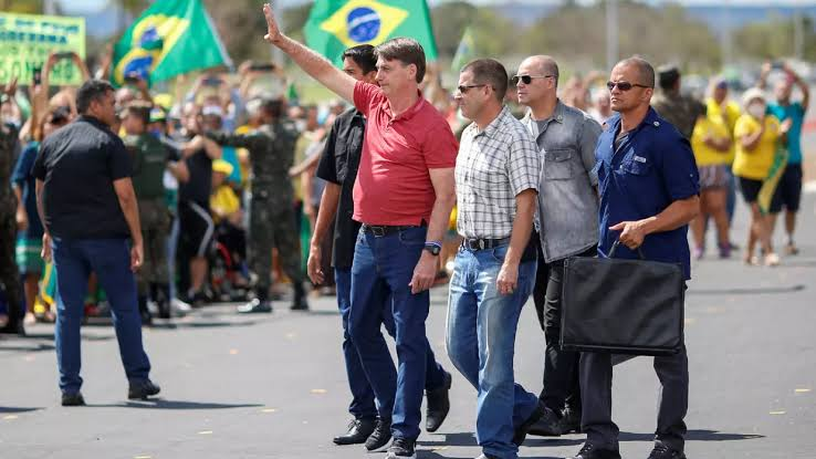 Brazil's President Jair Bolsonaro gestures after joining his supporters, who were taking part in a motorcade to protest against quarantine and social distancing measures, amid the coronavirus disease (COVID-19) outbreak, in Brasilia, Brazil April 19, 2020. © REUTERS/Ueslei Marcelino