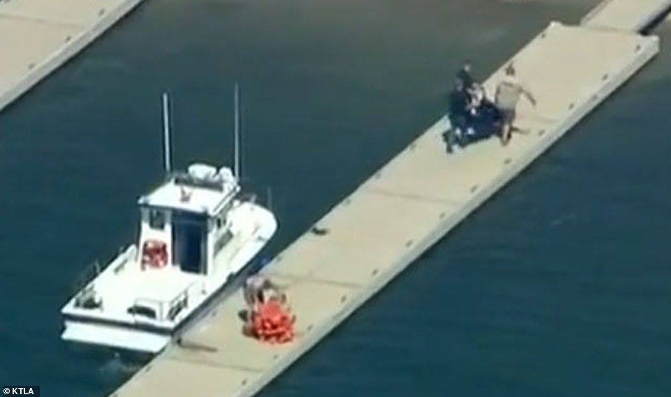 Authorities carry the body of Naya Rivera from a boat on Monday morning to be taken for formal identification